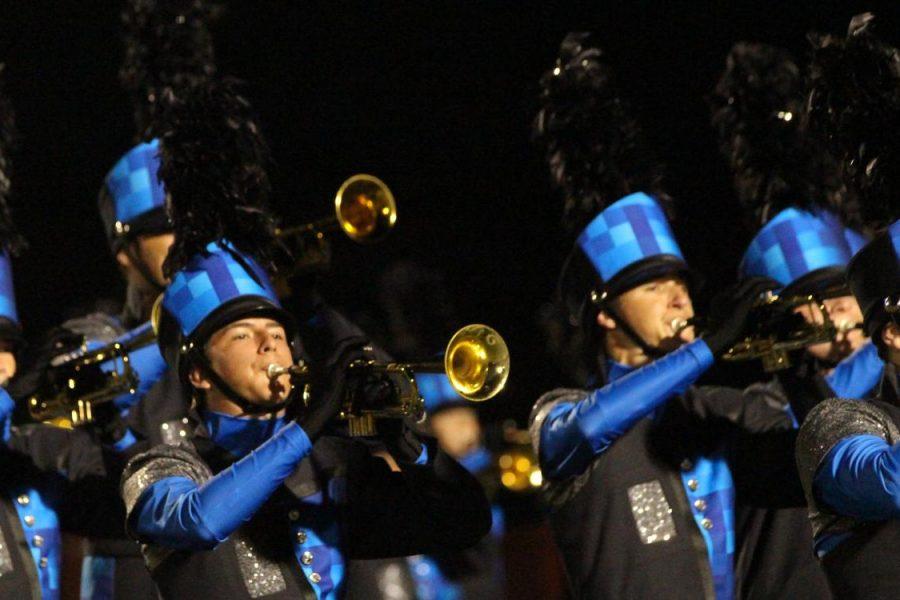 Band+members+display+their+uniforms+at+a+varsity+football+game
