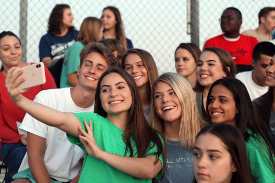 Sitting+in+the+bleachers+on+the+soccer+field%2C+a+group+of+seniors+pose+for+a+picture+of+the+sunrise.
