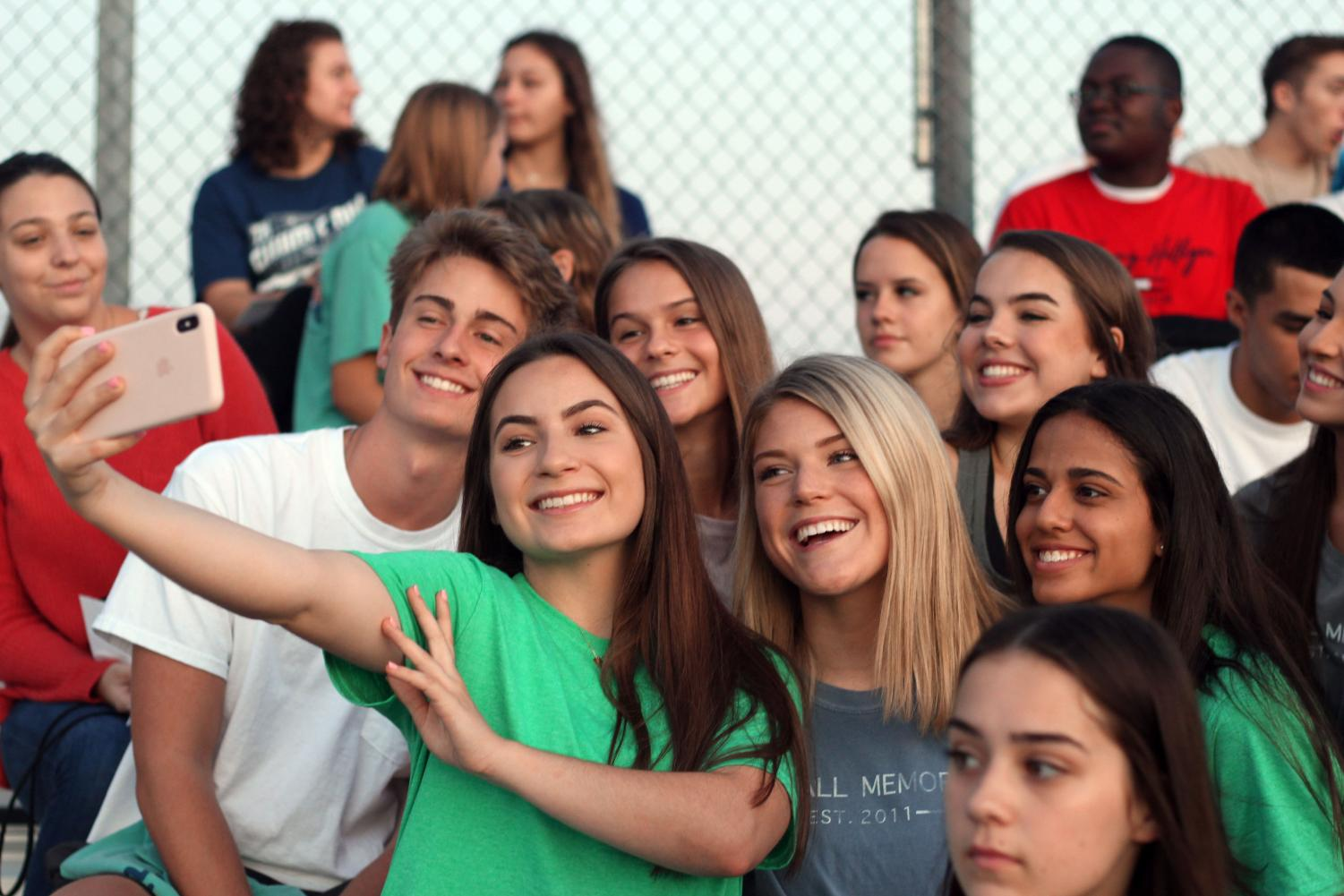 Sitting in the bleachers on the soccer field, a group of seniors pose for a picture of the sunrise.