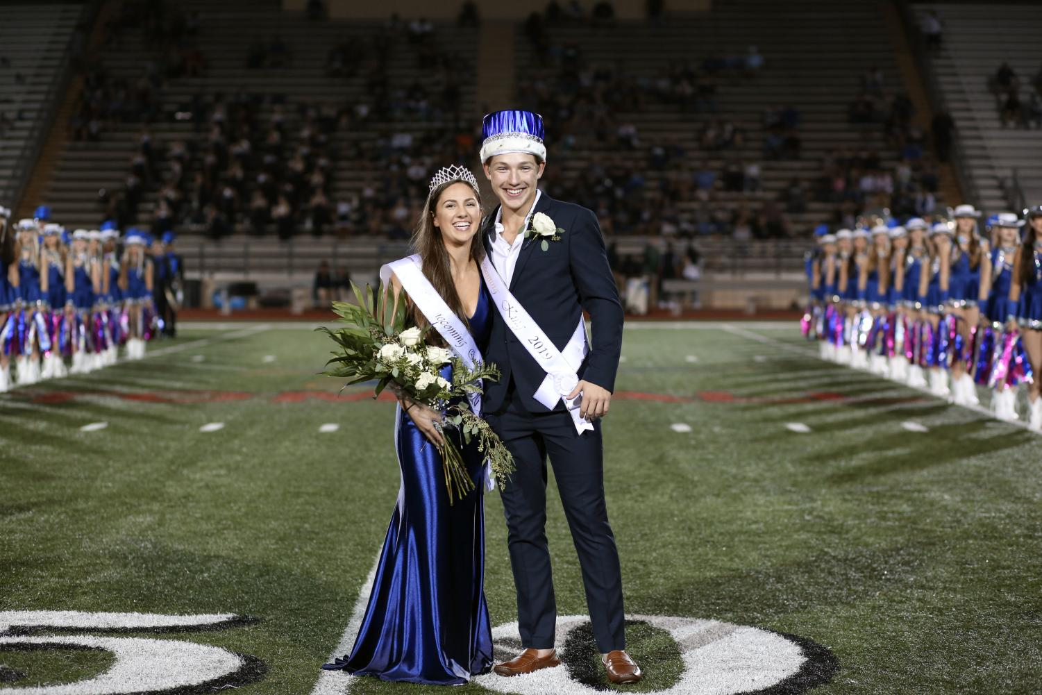 Seniors Halli Landry and Luke Sebesta, the homecoming king and queen, look toward the audience at halftime.
