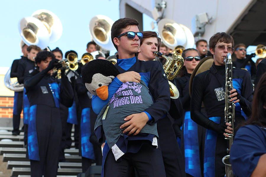 Senior and drum major Matthew Mendez hugs a stuffed penguin in the stands.