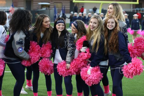 Varsity cheerleaders gather at a football game.