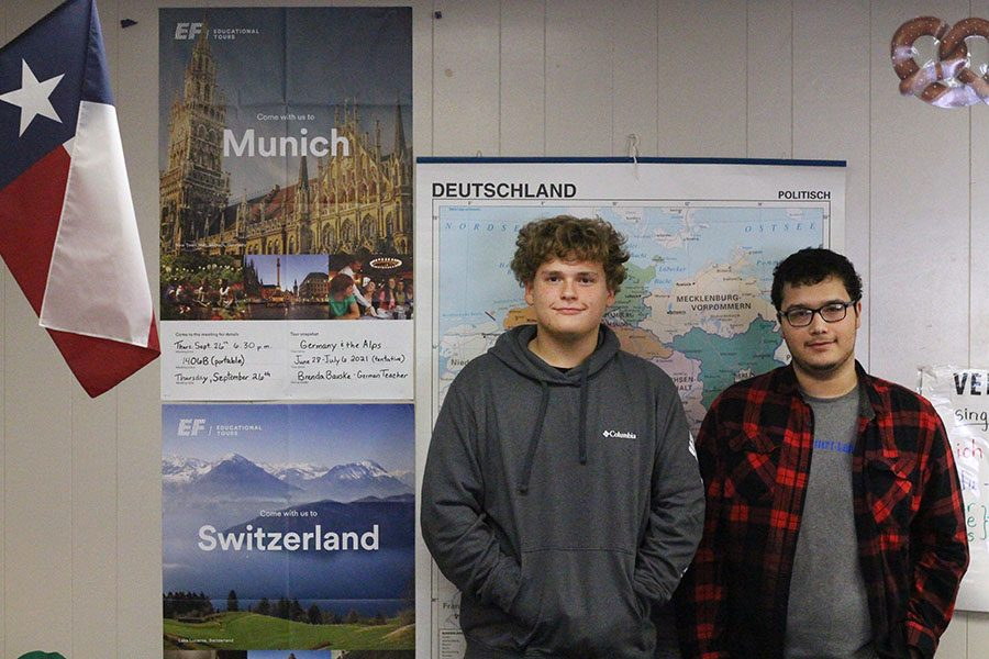 Sophomore+James+Eichmann+and+junior+Zachary+Charles+pose+in+front+of+the+poster+for+the++European+trip+they+are+attending.