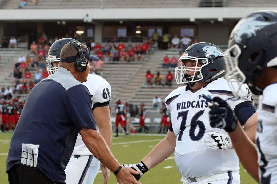 Junior Cameron Corrolla high-fives his coach before taking the field.