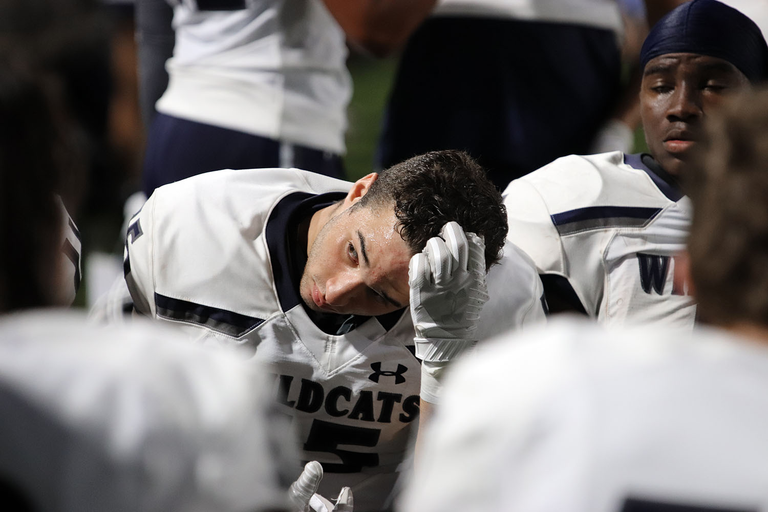 During a football game, junior John Boehning sits with his teammates and eyes the field.