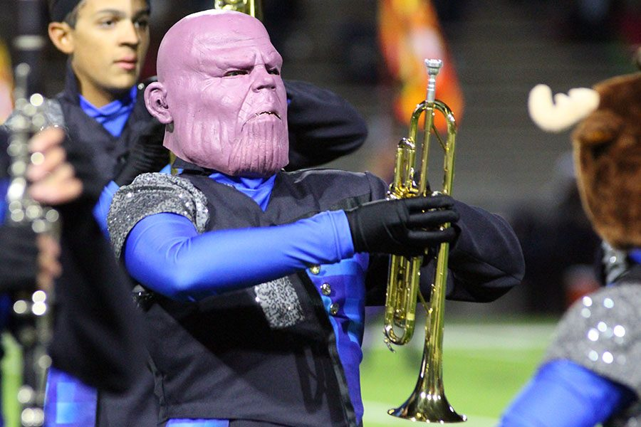Freshman trumpet player Julian Rivera marches while dressed as Thanos during halftime. Band members wore masks and hats in the spirit of Halloween.