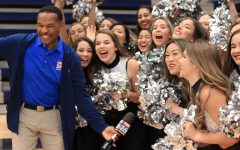 Members of the drill team cheer for the cameras with reporter Nate Griffin.