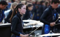 "As the marching band roars behind her, senior Abby Cascarelli plays the marimba at the Langham Creek football game. ""I love everyone in the front ensemble and performing with them is exhilarating,"" Cascarelli said. The Wildcats won the football game and have only lost one game this year."