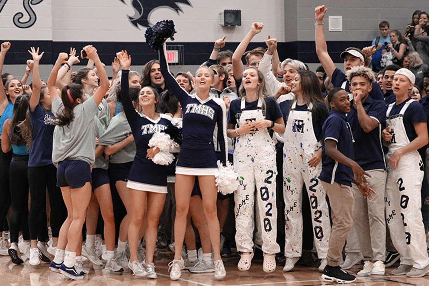 """The Navy Empire cheers for the senior class during the pep rally on Friday, November 15th. """"We loved being loud and obnoxious,"""" senior Brooke Forsyth said. The Navy Empire, created to increase school spirit during pep rallies and football games, competed with the other grades to be the loudest and most spirited during the pep rally."""