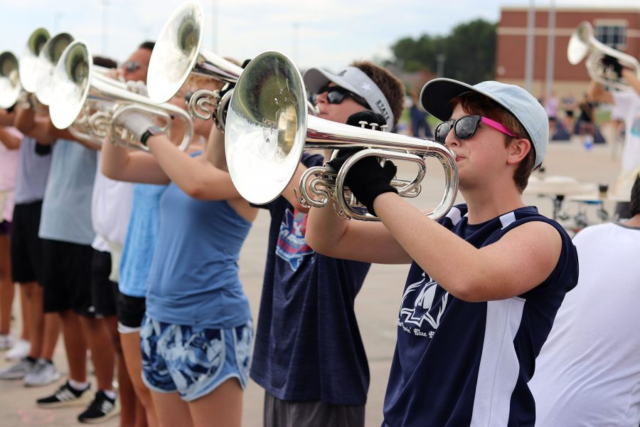 Standing in the hot sun, horn players form a line during band practice.