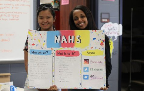 Two members of National Honor Society pose with a poster.