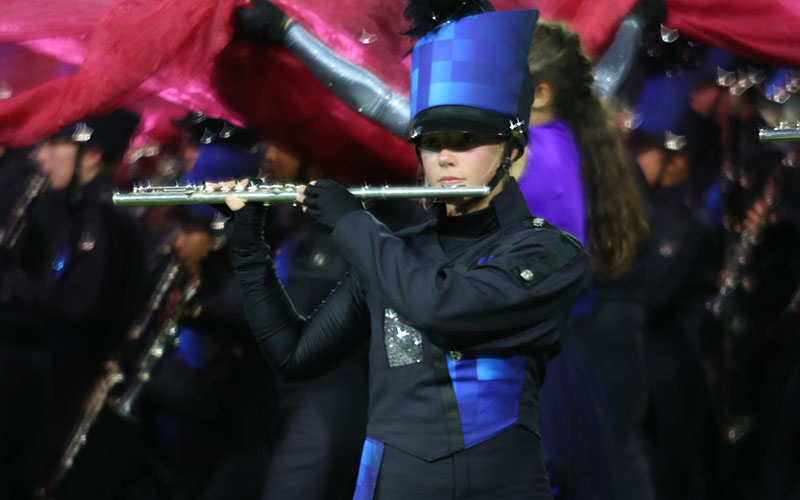 "Sophomore Hallie Mcleod is seen playing the flute, about to step off for the next drill. ""I had to focus really hard, because if I forgot where I was going next, it would mess up everything,"" said Mcleod.  It is Mcleod's second year in band."