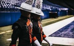 2014 graduate Spencer Holyoak walks into a stadium as drum major for the Crossmen Drum and Bugle Corps.
