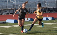 Junior Alexa Riddle prepares to kick the ball at soccer practice.