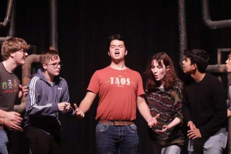 Members of the musical cast act out a scene at rehearsal.