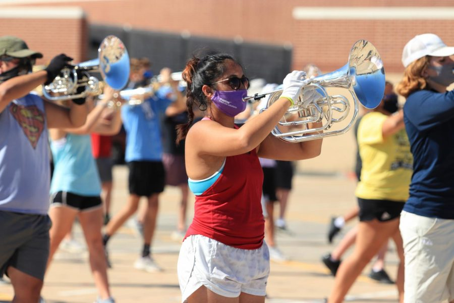 Band students warm up before rehearsing this year's show at practice. A number of students in band and other activities chose to both learn at home and attend practice in person.