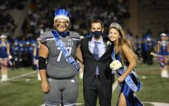 Senior homcoming king and queen Cameron Cook and Lauren Crawford pose with principal Dr. Metz.