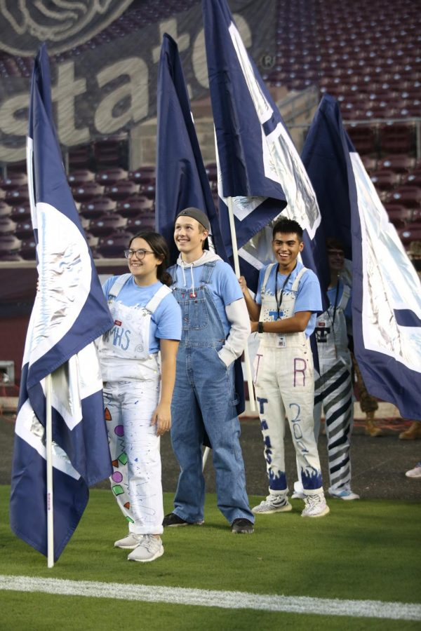 Student council members laugh while setting up flags in the stands.