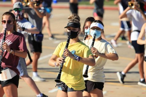 Junior clarinet player Morgan Larsen marches with a mask during a rehearsal.