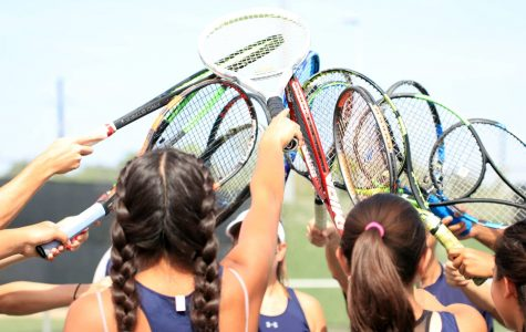 The varsity tennis team puts their racquets together to break out before their first match of the season against Klein Cain.