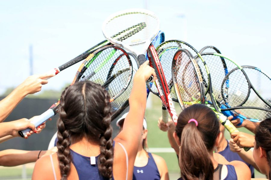 The+varsity+tennis+team+puts+their+racquets+together+to+break+out+before+their+first+match+of+the+season+against+Klein+Cain.+