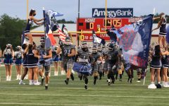 Varsity football players run through a sign at the start of the first game.