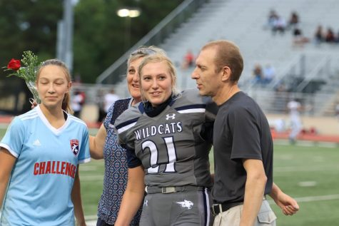 Senior Lorelai Stamrood poses with her family at the first football game of the year.