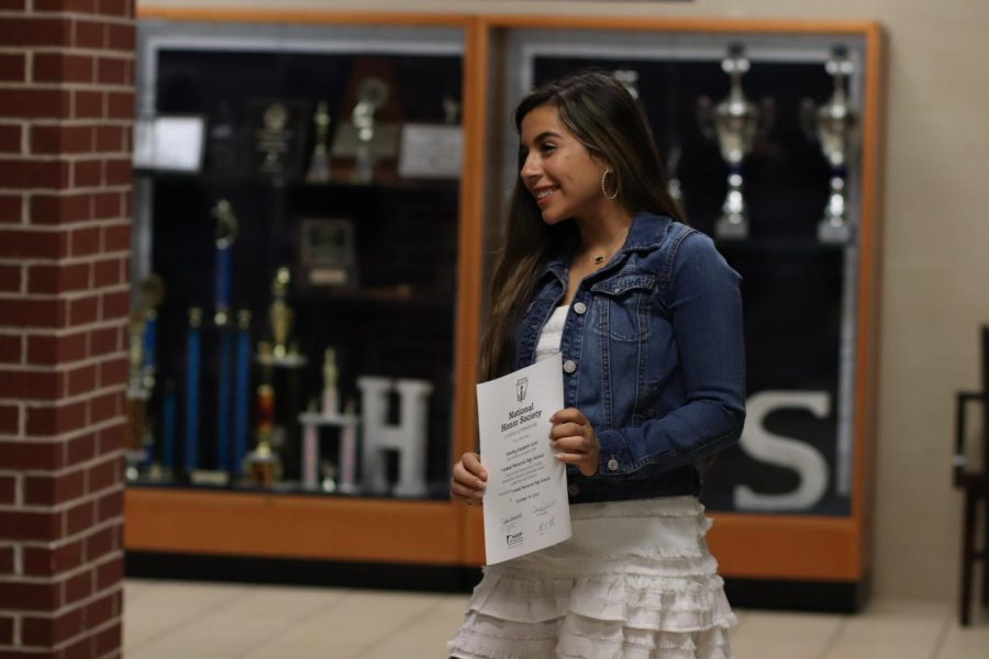 A newly inducted NHS member poses after receiving her certificate.