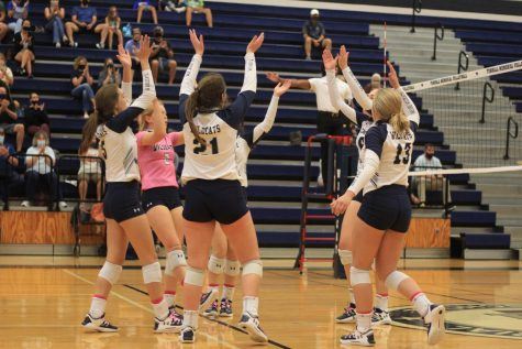 Volleyball players celebrate after scoring a point.