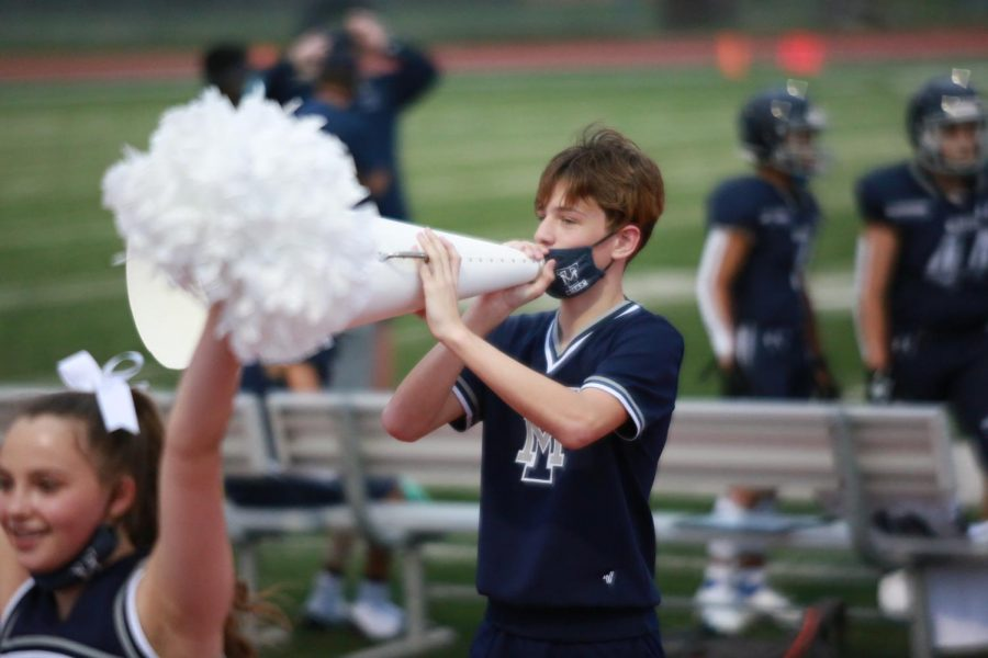 Freshman cheerleader Evan Flett cheers on the sidelines at a football game.
