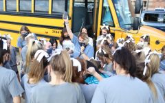 Cheerleaders pay attention to their coach before heading on the bus.