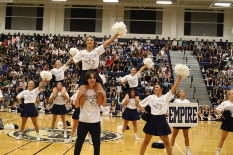 The varsity cheerleaders rally with the crowd to get them hyped for the game.